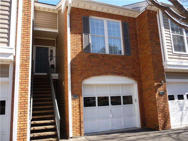 Brick and vinyl condo has a 1-car garage on main level; living area on upper level