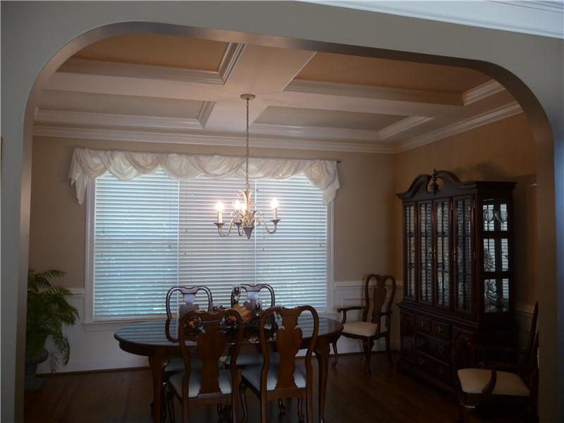 Arched entry into dining room which has an elegant coffered ceiling and hardwood flooring.  Triple windows here too.