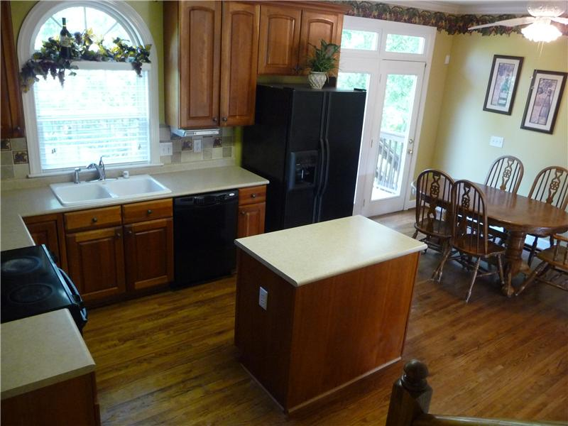 Eat-in kitchen has an island, lots of cabinets, hardwood floors and a large walk-in pantry. French doors open to the deck.