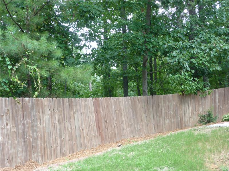 Privacy fence and wooded back yard.