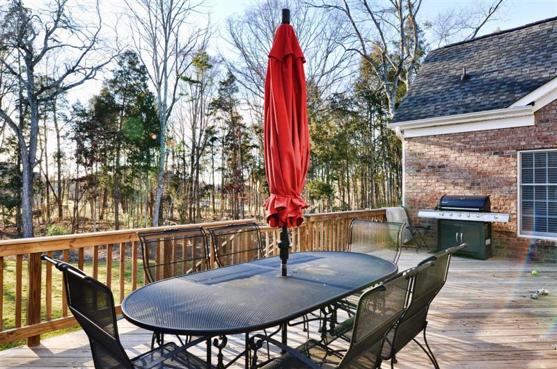Wood deck overlooks the well landscaped backyard; home is on over an acre and is in a cul-de-sac