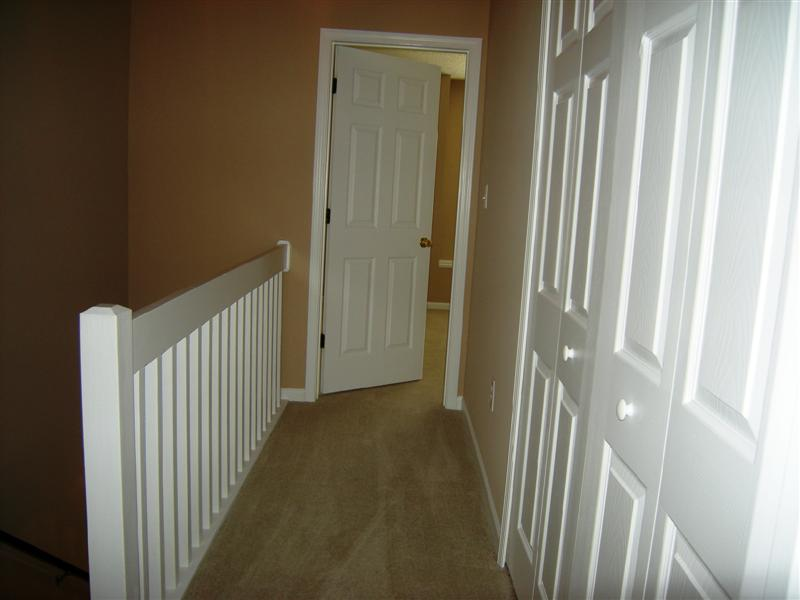 Carpeted hallway on the upper level with laundry closet